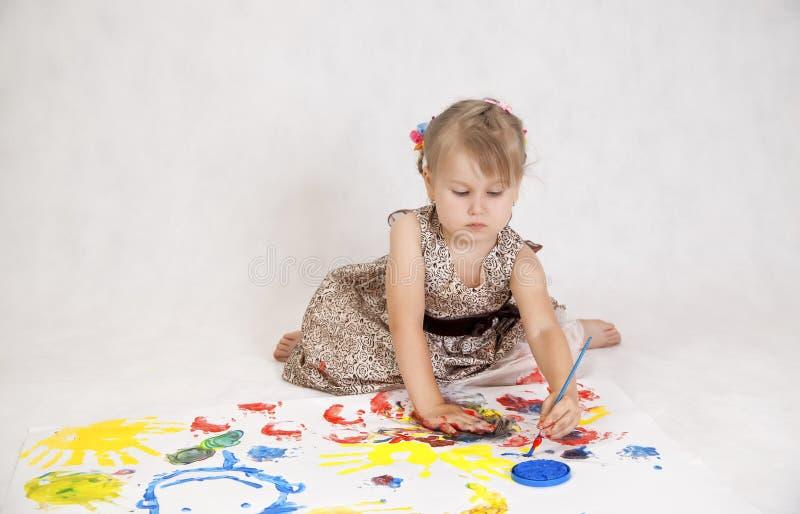 小美丽的女孩画油漆,在油漆的手 免版税库存图片