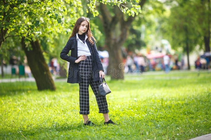 小美丽的时髦的孩子女孩画象有太阳镜和短的方格花纹裤的在绿色森林背景的城市公园 免版税图库摄影