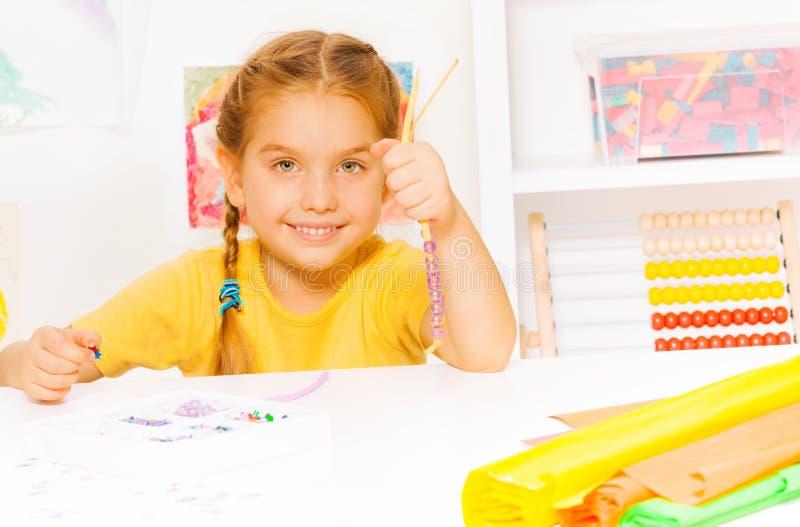 小美丽的白肤金发的女孩在串上把小珠放 免版税库存图片