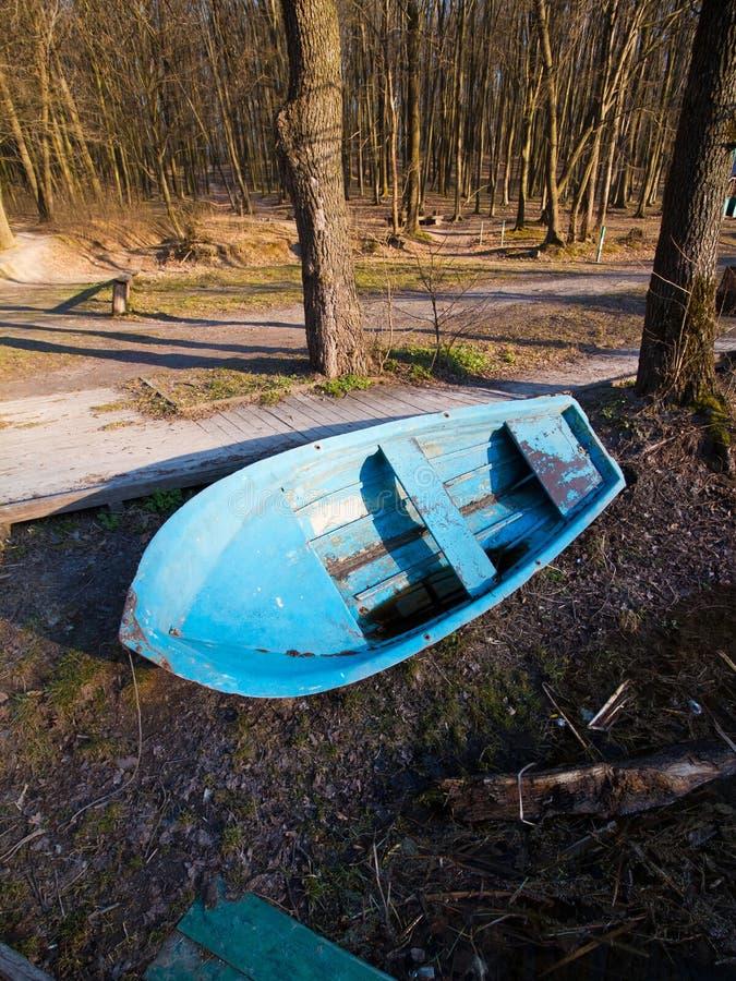 小老破旧的破旧的木救助艇,绘了与光秃的树的蓝色,早春天风景在河的河岸 免版税库存图片