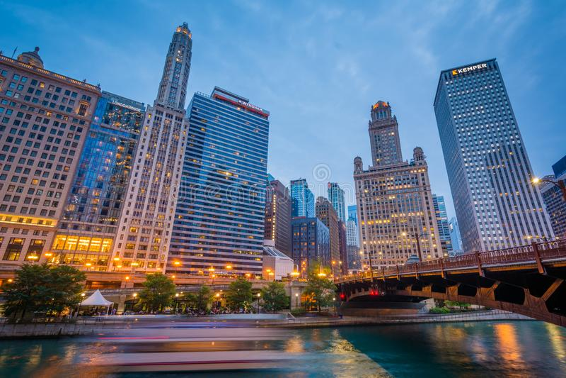 小船交通和摩天大楼沿芝加哥河在晚上在芝加哥,伊利诺伊 免版税库存图片
