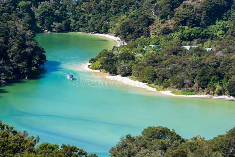 小船令人惊讶的看法在一个绿松石盐水湖在亚伯塔斯曼国家公园,新西兰 免版税图库摄影