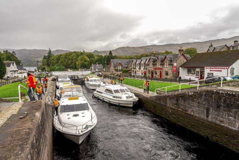 小船停放在等待的锁和的人民之间送进古苏格兰运河在堡垒奥古斯都在奈斯湖,苏格兰附近 库存照片