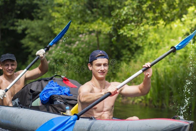 小船划船桨的年轻运动人沿河在夏日 独木舟 朋友在皮船游泳 免版税库存照片