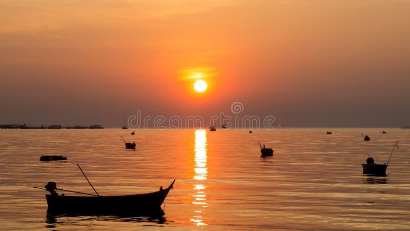 小船剪影在暮色时间的海与美好的太阳和反射 库存图片