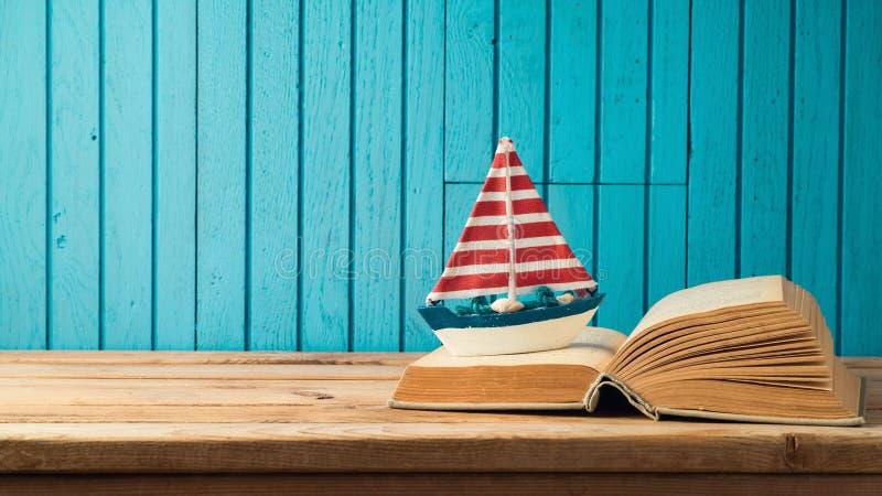小船和书在木桌上 免版税库存图片