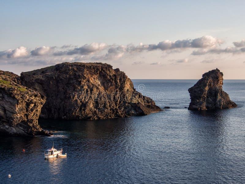 小船和岩石在地中海 潘泰莱里亚海岛,意大利 库存照片