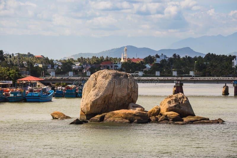 小船和岩石近的渔村河的Kai在Nha Tra 免版税库存照片