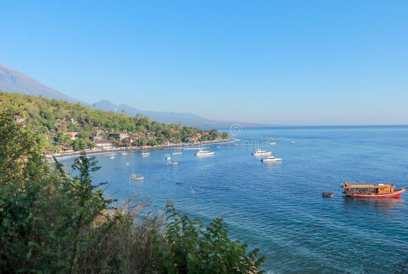 小船和快艇停泊在Jemeluk海湾在巴厘岛 绿松石海颜色和安静海湾 密林和背景与山 免版税库存照片