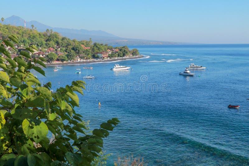 小船和快艇停泊在Jemeluk海湾在巴厘岛 绿松石海颜色和安静海湾 密林和背景与山 库存图片