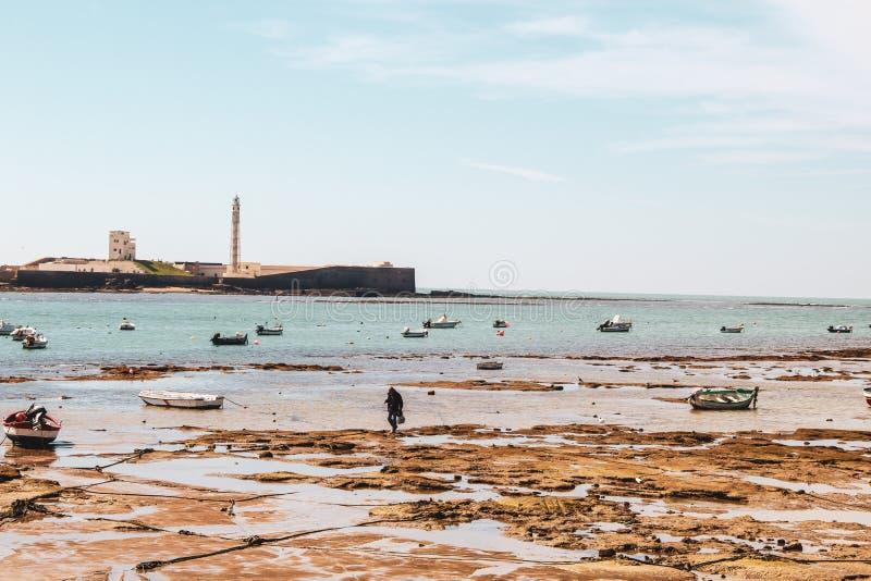 小船和浪潮在海滩卡迪士在安大路西亚,西班牙 库存图片