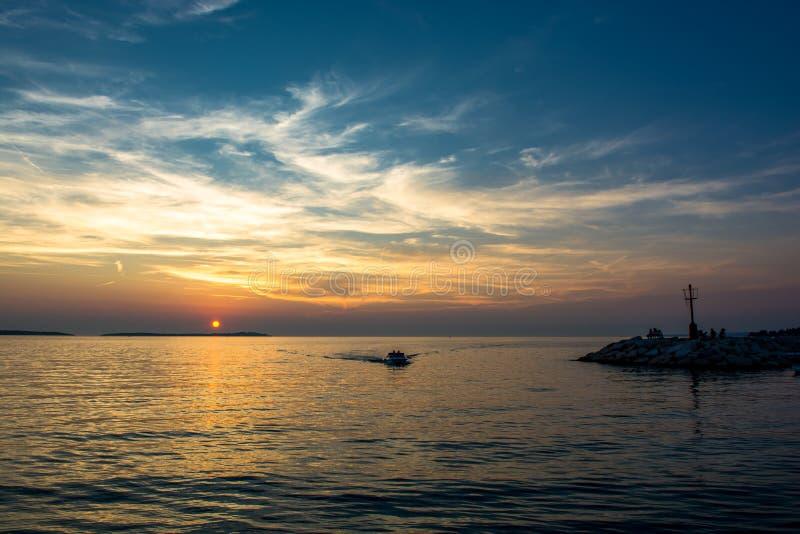 小船回到港口在日落在克罗地亚 免版税库存照片