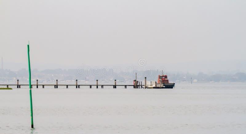 小船在一艘浮船停泊了在Poole港口 库存图片
