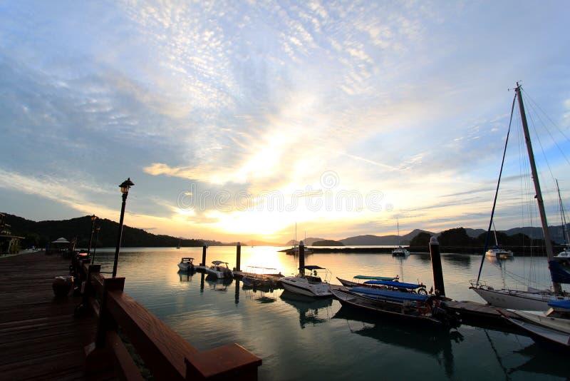 小船在小游艇船坞靠码头反对日出天空 免版税库存照片