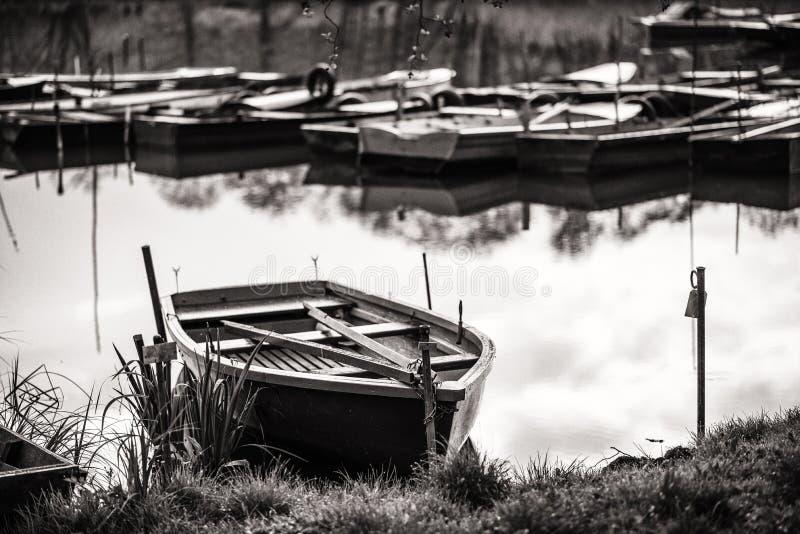 小船港口-在湖的黑白木小船的 图库摄影