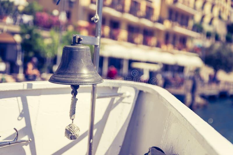 小船游览:与小船响铃的小船在天蓝色的大海的弓,看法,山脉和小的村庄 拉戈di加尔达,意大利 库存图片