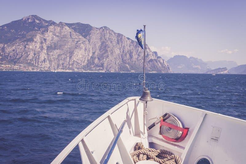 小船游览:小船弓、看法在天蓝色的大海和山脉 拉戈di加尔达,意大利 免版税图库摄影