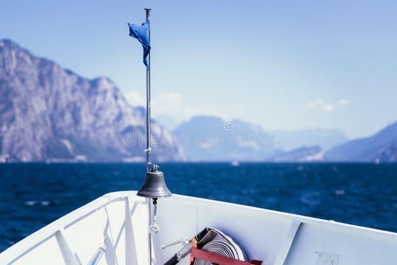小船游览:小船弓、看法在天蓝色的大海和山脉 拉戈di加尔达,意大利 免版税库存照片