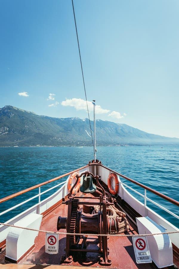 小船游览:小船弓、看法在天蓝色的大海,村庄和山脉 拉戈di加尔达,意大利 免版税图库摄影