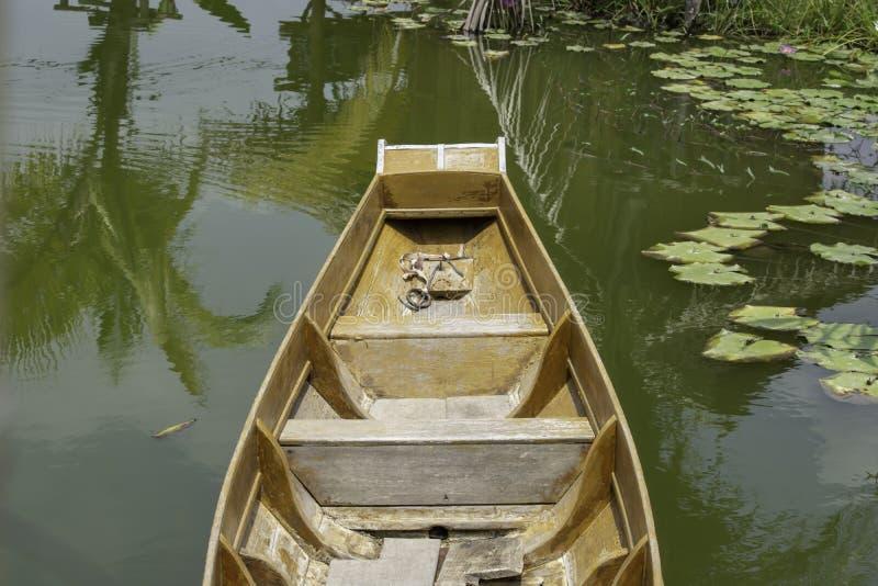 小船漂浮做了的木头在水在荷花池 库存图片