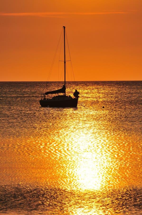 小船现出轮廓的日落 免版税库存图片