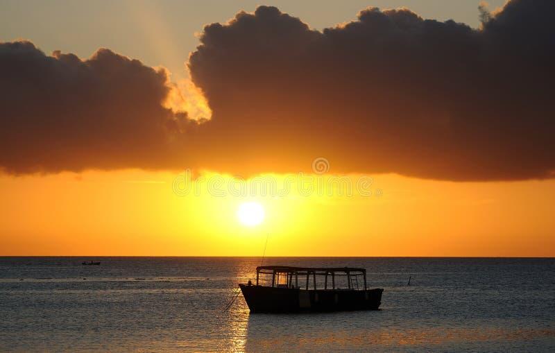 小船现出轮廓的日落 免版税图库摄影