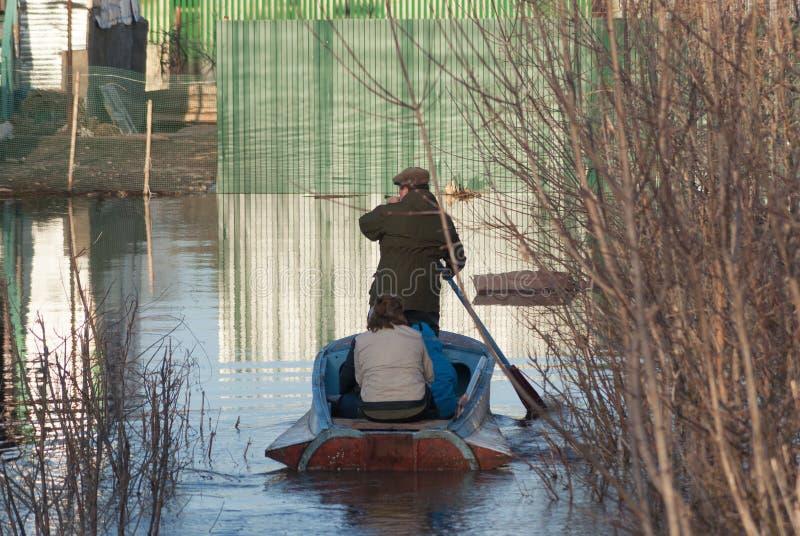 小船的人们沿一条被充斥的街道航行到他们的房子 凹下去的下面水篱芭街道房产 春天洪水河 库存图片
