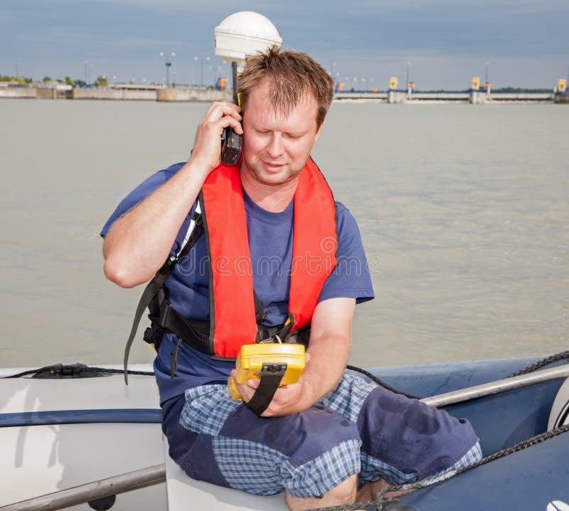 小船的人在测量与GPS 免版税库存照片