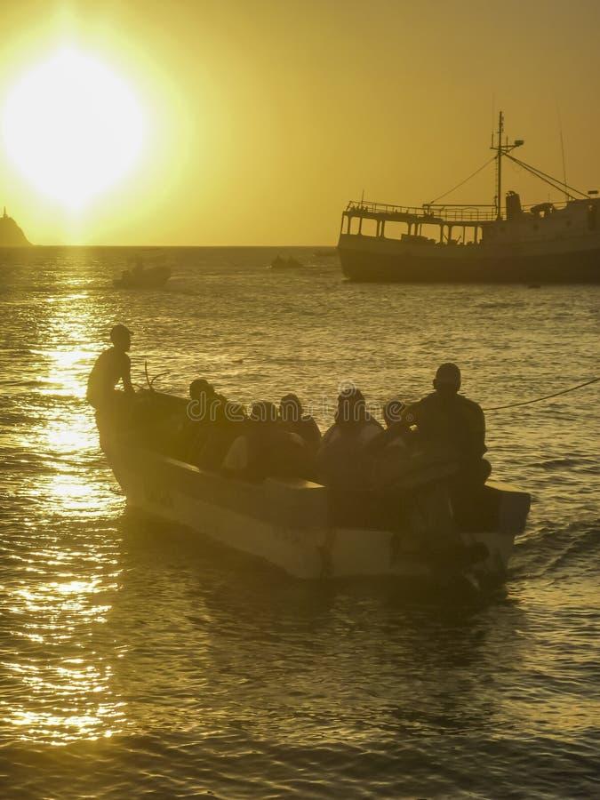 小船的人们在Taganga海湾哥伦比亚的日落 库存照片