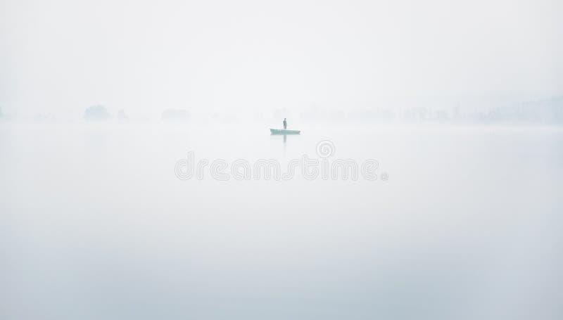 小船的单独渔夫在湖的大雾在一个秋天早晨 免版税库存图片