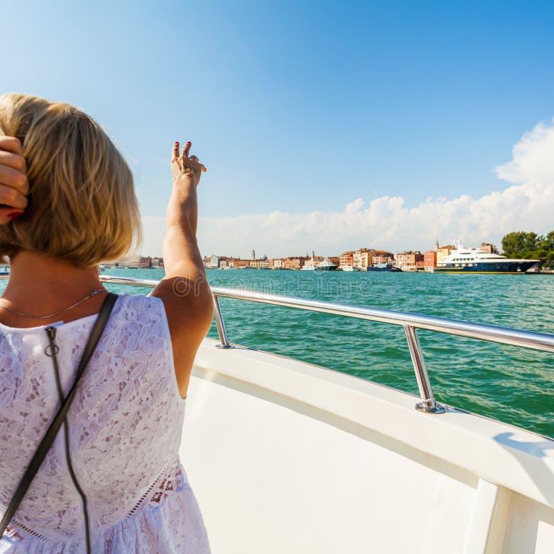 小船的女孩显示她的手到威尼斯 免版税库存照片