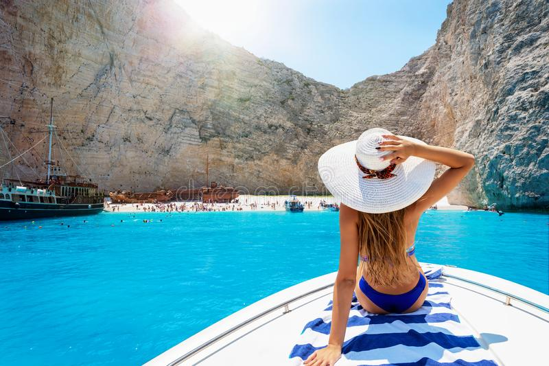 小船的妇女享受看法对海难海滩,Navagio在扎金索斯州,希腊 免版税图库摄影