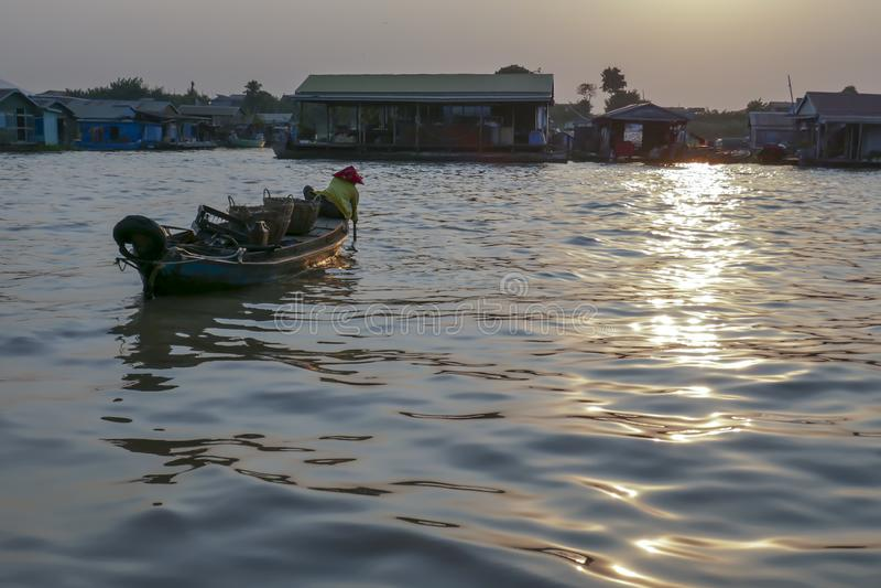 小船的妇女通过Tonle Sap河浮动渔村在柬埔寨 免版税库存图片