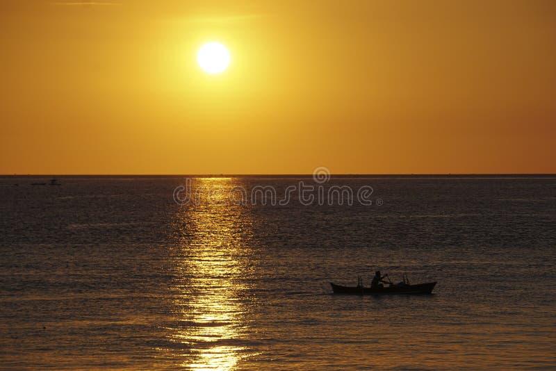 小船的渔夫,当日落 免版税库存图片