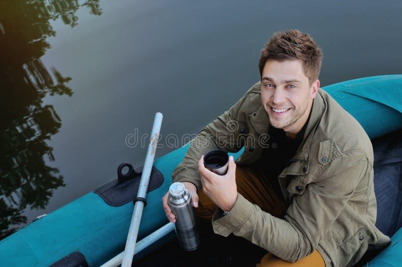 小船的英俊的可爱的人在湖,生活方式 库存图片