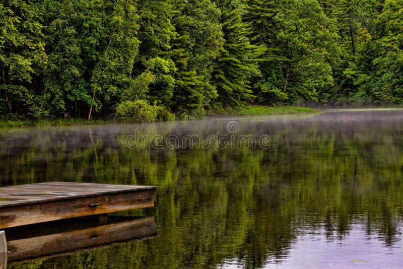 小船码头例证有薄雾的池塘 库存图片