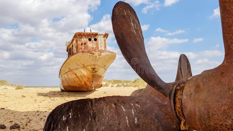 小船老击毁在沙子的在咸海 库存照片