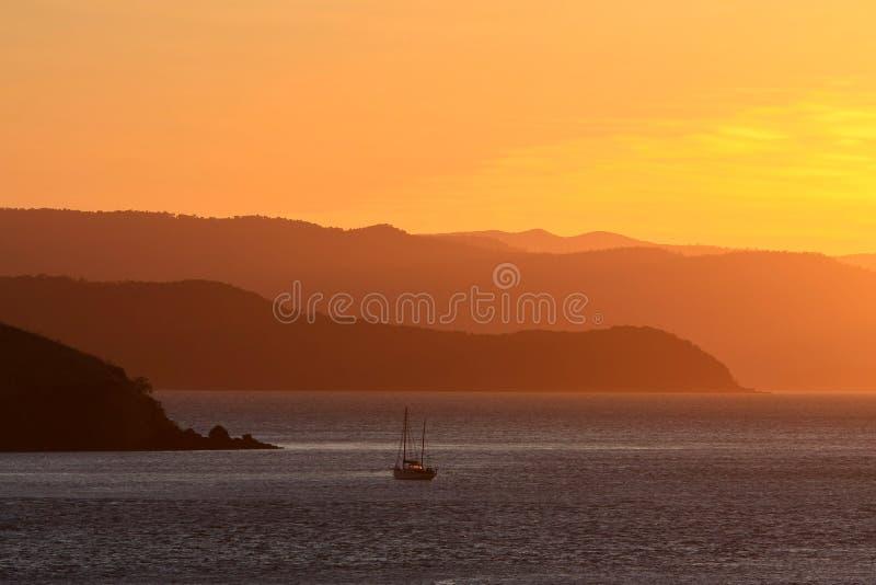 小船航行日落的距离小山 库存图片