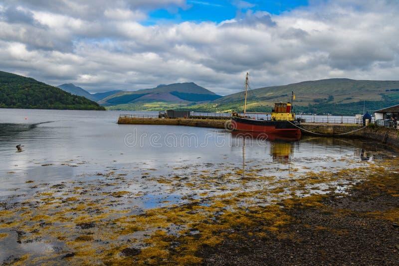 小船被停泊反对有山的一个码头在背景中 图库摄影