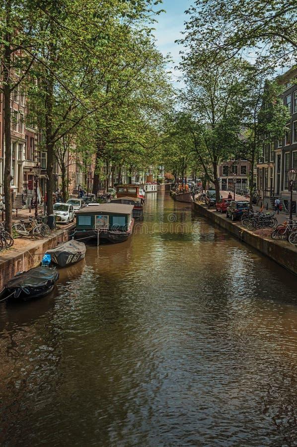 小船被停泊在运河和砖瓦房的边在阿姆斯特丹 免版税库存照片