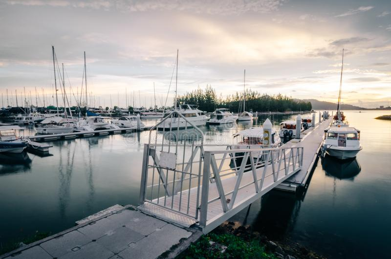 小船靠了码头在游艇俱乐部有美好的日落背景 免版税库存照片