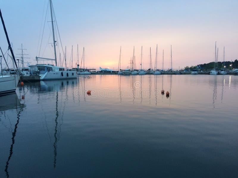 小船,小游艇船坞在黎明,日出云彩,塞萨罗尼基希腊 库存图片