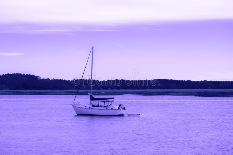 小船 汽船在紫罗兰色天空的一条河和反射向河 免版税库存照片