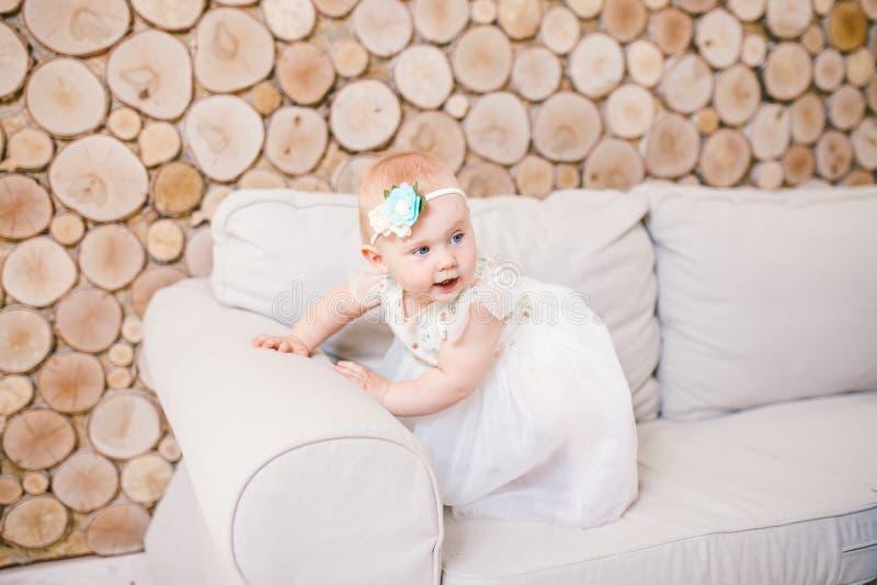 小蓝眼睛的女孩白肤金发在有装饰的一件白色薄纱礼服在她的使用和高兴在一个米黄沙发的头在屋子w里 免版税库存照片