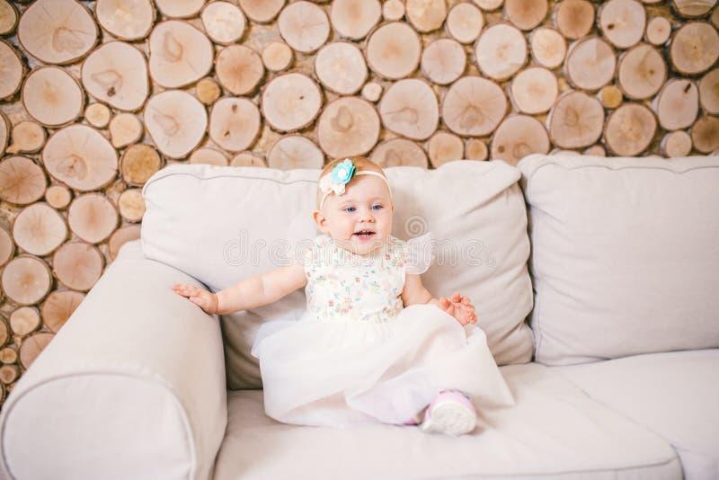 小蓝眼睛的女孩白肤金发在有装饰的一件白色薄纱礼服在她的使用和高兴在一个米黄沙发的头在屋子w里 库存照片