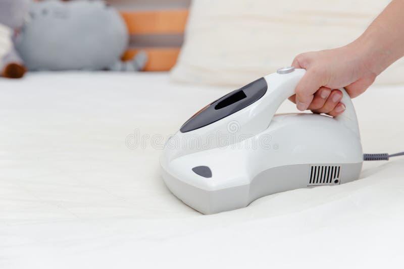 小蜘蛛使用清洁床床垫的吸尘器 免版税库存图片