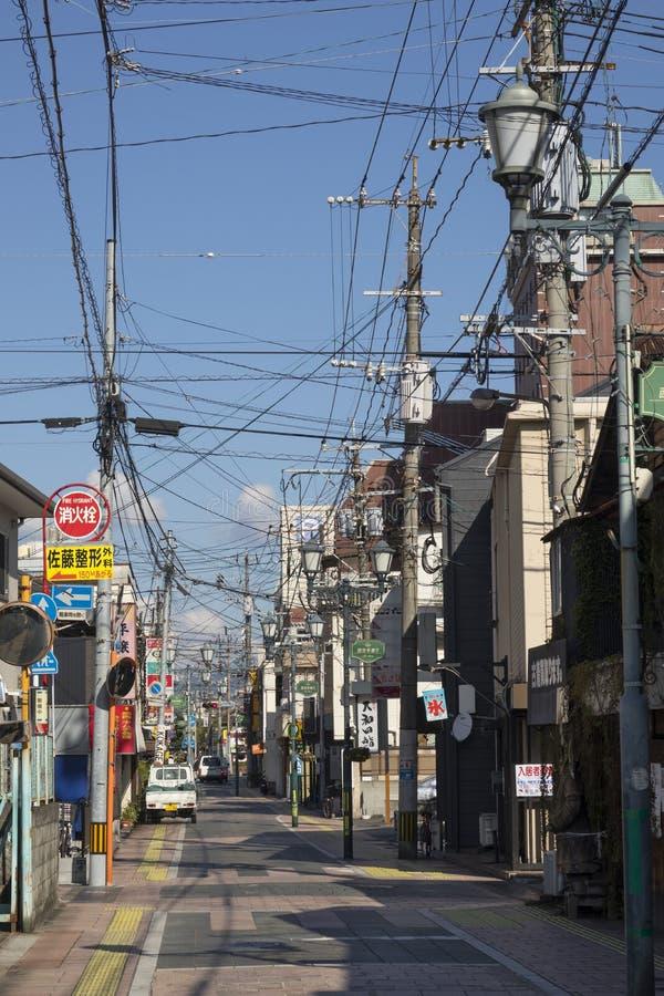 小街道在别府的中心有标志和许多的电导线 免版税库存图片