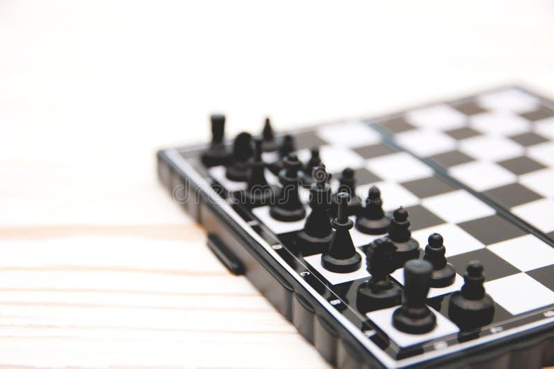 小装在口袋里棋,在白色木背景的一杆棋枰安置的塑料棋子 免版税图库摄影
