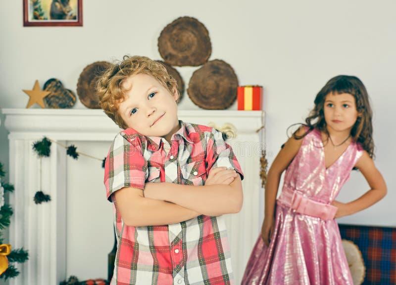 小跨武装的卷曲男孩和女孩使用并且摆在得户内 儿童` s友谊的概念 库存照片