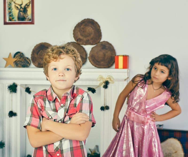 小跨武装的白种人卷曲男孩和女孩使用并且摆在得户内 库存图片
